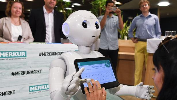 """Der humanoide Roboter """"Pepper"""" begrüßt Shopper im """"Merkur""""-Markt."""