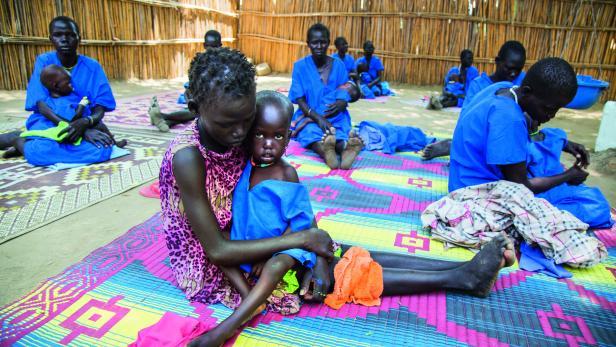 HILFE IN DER NOT: Südsudanesische Frauen in blauem Spitalsgewand kümmern sich um ihre unterernährten Kinder.