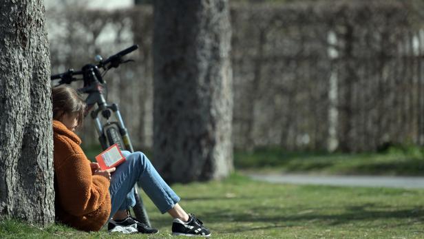 Eine Parkbesucherin auf der Wiese vor dem Augarten der Bundesgärten