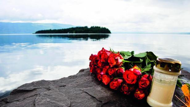 Rosen und eine Kerze als Gedenken auf der Insel Utøya